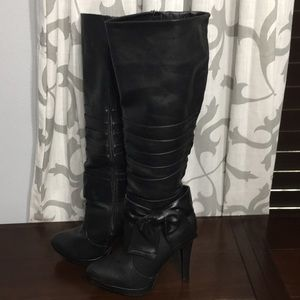 Knee-high black boots with bow accent